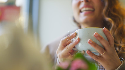 Female hands holding a cup whilst talking happily