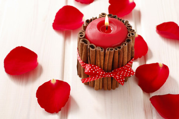 Red scented candle decorated with cinnamon sticks. Rose petals a