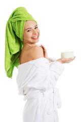 Woman in bathrobe applying cream on shoulder