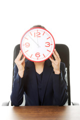 Businesswoman sitting with big clock at the office