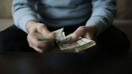 A businessman's hands counting hundred dollar bills at a table
