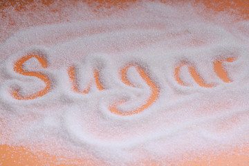 "The word ""Sugar"" written in sugar grains. Overhead view."