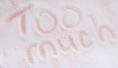 "The words ""too much"" written in sugar grains. Overhead view."