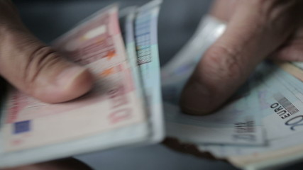 Old man's hands counting euro banknotes.