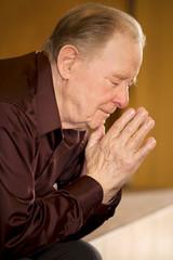 Elderly man praying in church