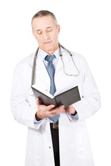 Mature male doctor reading notes