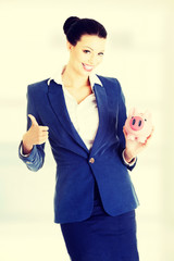 Businesswoman saving money in a piggybank.