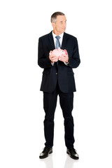 Full length confused businessman holding piggybank