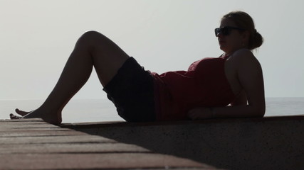 Silhouette of young woman relaxing on the coast.