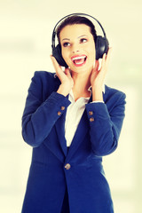 Happy businesswoman listening to the music.
