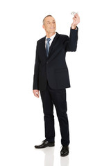 Full length businessman holding small airplane