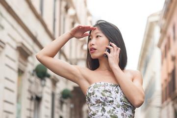 Young beautiful asian woman talking using mobile phone spring ur