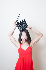 Young beautiful asian woman red dress smiling with clapperboard
