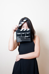 Young beautiful asian woman black dress eyes with clapperboard