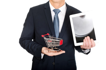 Close up man holding shopping cart and tablet