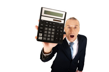 Shocked businessman holding a calculator