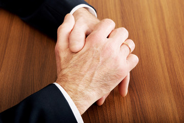Close up of businessman clenched hands on the desk