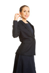 Young businesswoman holding house key.