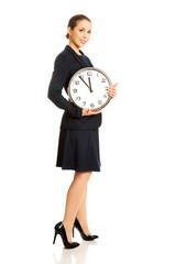 Business woman holding big clock.