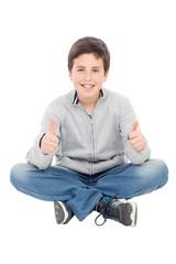 Smiling preteen boy sitting on the floor saying Ok