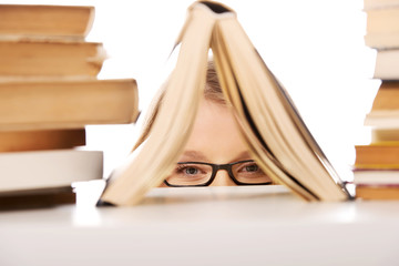 Young woman hiding behind a book