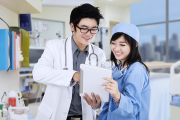Asian doctors with tablet in clinic