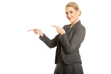 Business woman pointing at copyspace on the left