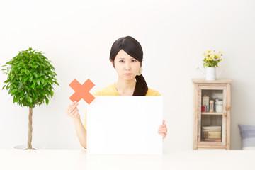 メッセージボードとバツ印を持つ女性