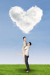 Couple having fun under heart shaped cloud
