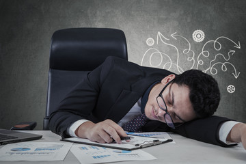 Confused manager sleeping on desk