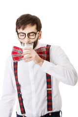Man wearing suspenders drinking milk.