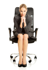 Sitting businesswoman with hands on chin