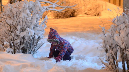 Happy beautiful little girl throws snow in winter, night lightin