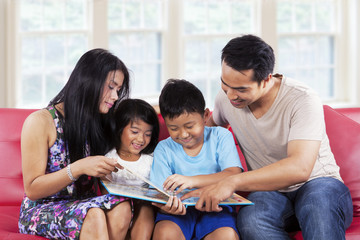 Family enjoy read a story book together