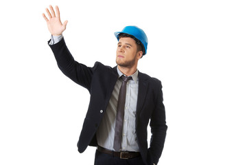 Businessman in hard hat showing copyspace.