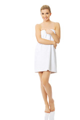 Spa woman wrapped in towel pointing to the left.