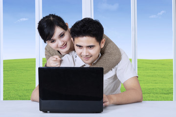 Handsome man using laptop with girlfriend