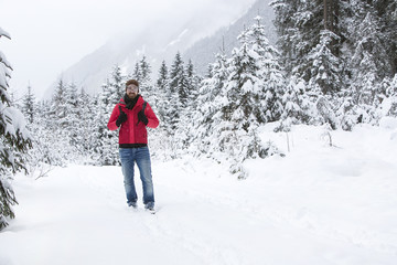 Young man with snow glasses hiking in wintry forest landscape