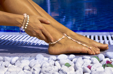 Woman posing by the pool with bracelets