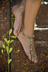 Woman posing on stone step with bracelet on ankle