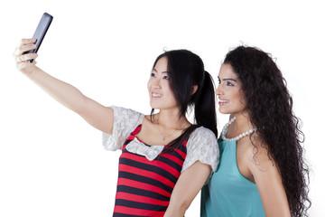 Multi racial girls taking photos in studio