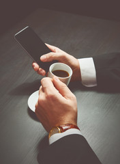 phone and a cup of coffee in the hands of a businessman in dark