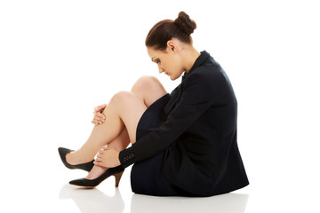 Tired businesswoman sitting on the floor.