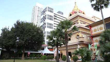 Buddha temple in Penang among palms at the background of skyscra