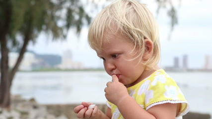 closeup little blonde child eats at background of bay and city u