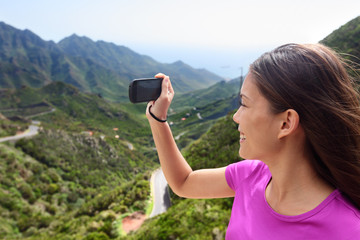 Girl taking smartphone picture of mountain nature