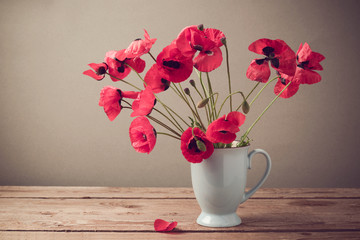 Poppies in cup on wooden table