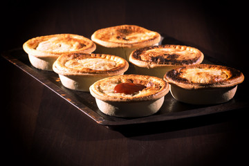 Freshly baked meat pies with sauce and high contrast lighting.