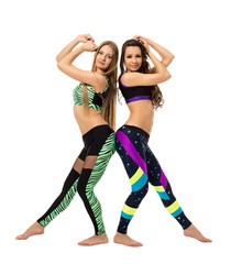 Two attractive fitness trainers posing barefoot