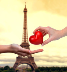 Hand donating heart. In the background Eiffel tower at sunset